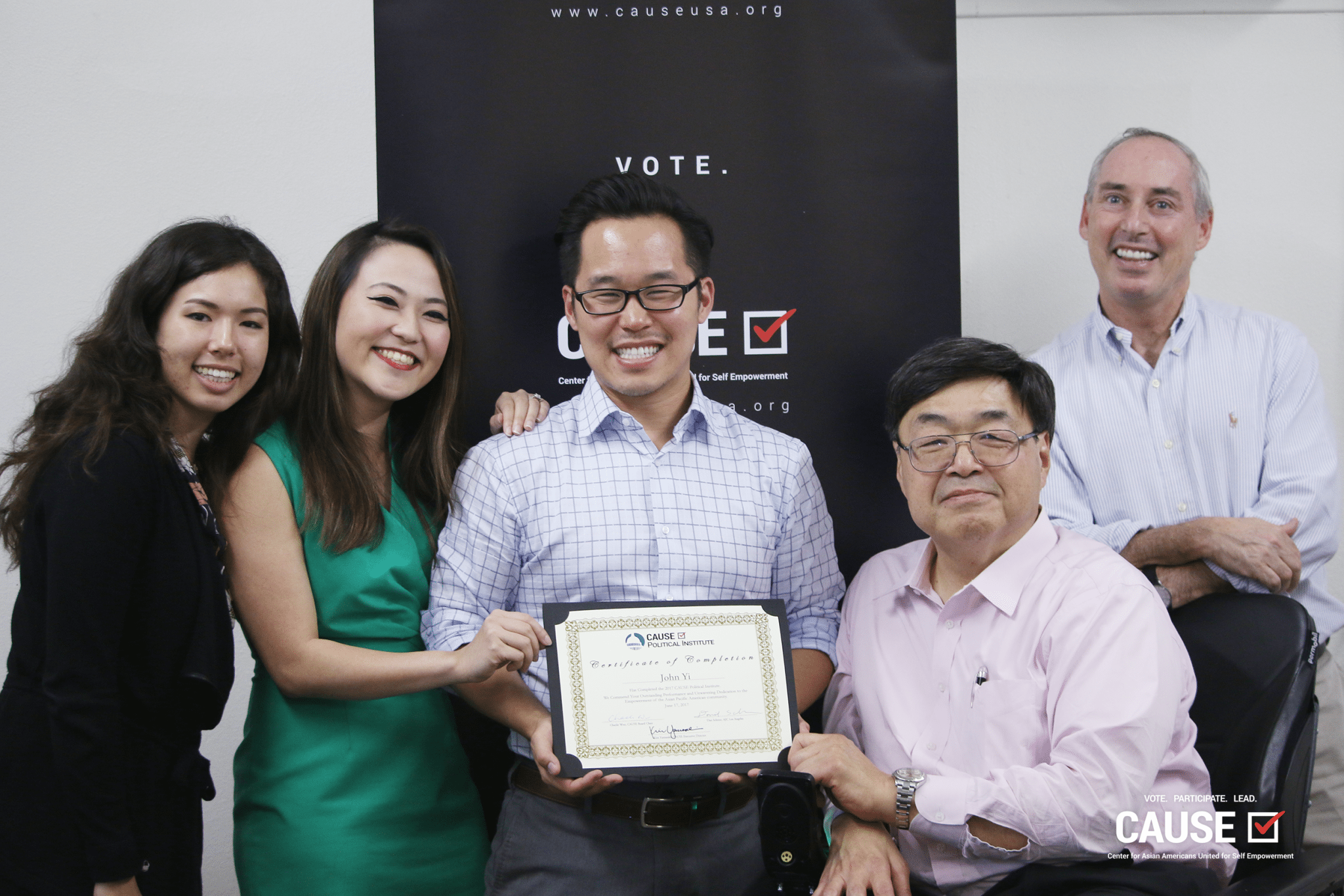 John Yi accepts his program completion certificate from CAUSE