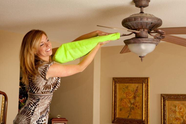 Woman cleaning ceiling fan